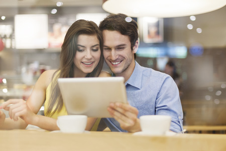Couple have fun with digital tablet in cafe  photo