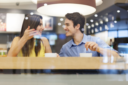 Young couple have interesting discussion in cafe  photo