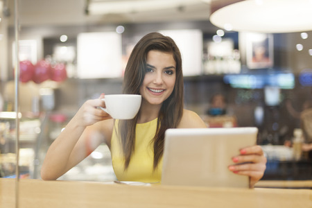 Portrait of beautiful woman in cafe with digital tablet  photo