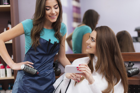 hair treatment: Female customer showing which hairstyle she wants on mobile phone