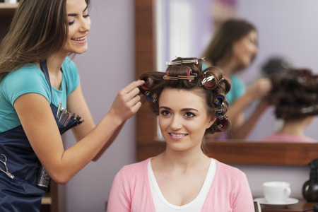 Creating trendy hairstyle by young woman  Stock Photo