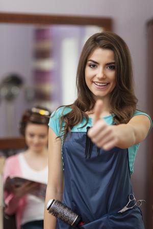 hand sign: Glimlachende vrouwelijke eigenaar van kapsalon OK handteken toont