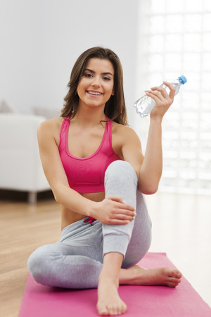 Portrait of beautiful woman after workout with bottle of water  photo