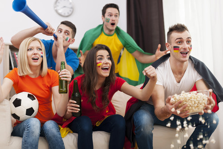 Friends of different nations supporting football team   Stock Photo