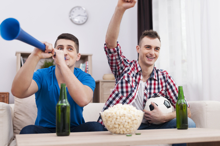 ecstatic: Ecstatic young men supporting soccer at home