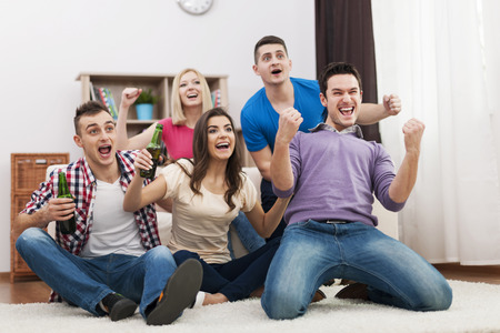 excitación: Jóvenes amigos viendo la televisión y animando fútbol