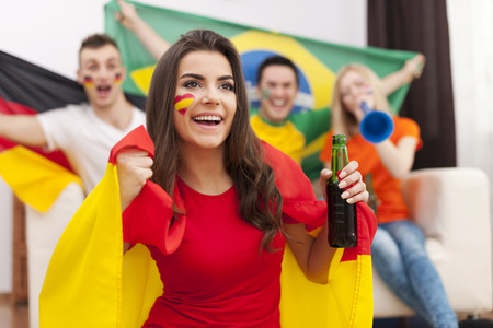 Beautiful spanish girl with her friends cheering football match  photo