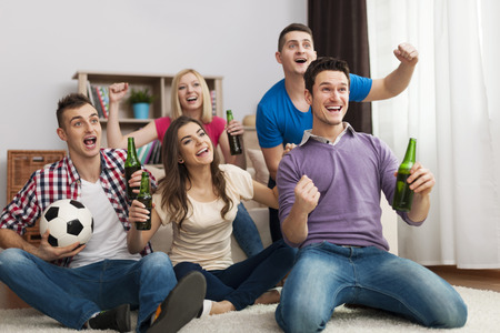 Group of friends enjoying soccer in TV    photo