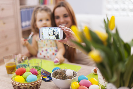 woman smartphone: Mother and daughter taking self portrait while easter time Stock Photo