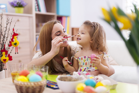 multi family house: Mother and her baby have fun while painting easter eggs