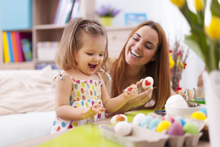 creative egg painting: Loving mother and her baby painting easter eggs