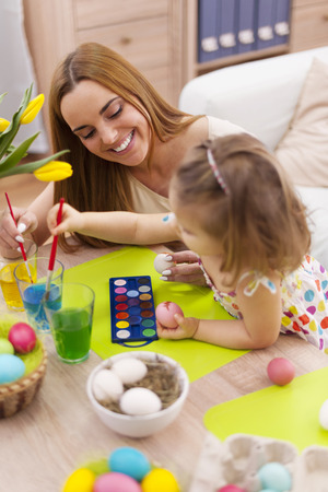 creative egg painting: Mother and her baby painting easter eggs Stock Photo