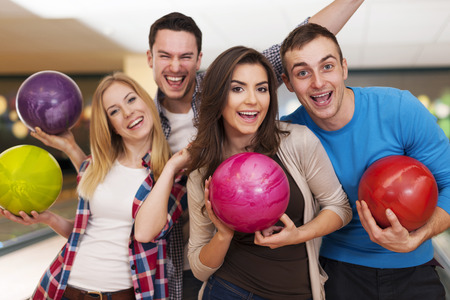 Happy friends bowling together photo