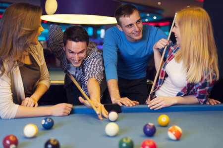 Group of four friends playing billiard photo