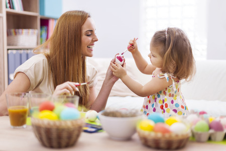 creative egg painting: Happy mother helping baby painting on easter eggs  Stock Photo