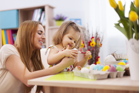 pussy willow: Focus little girl painting easter eggs with mother