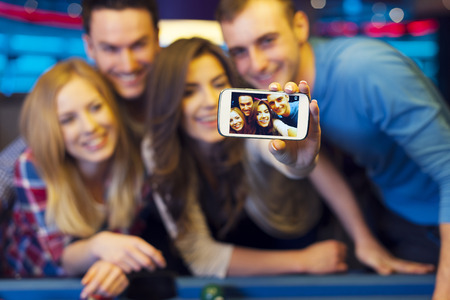 bending over: Smiling friends taking selfie photo from nightclub with billiard
