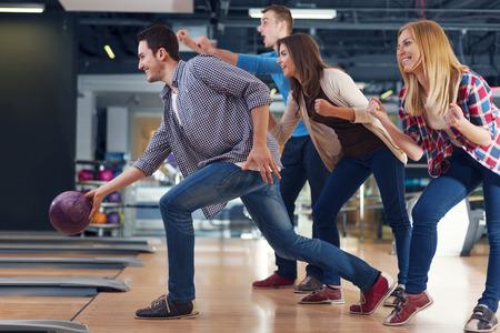 bolos: Amigos que animan a su amigo, mientras lanzaba la bola de bowling