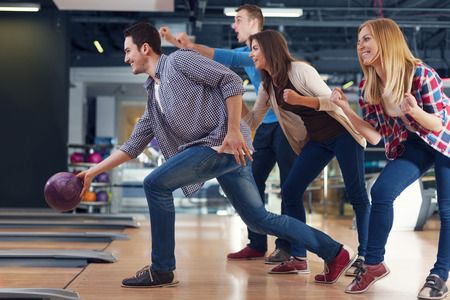 Friends cheering their friend while throwing bowling ball    photo