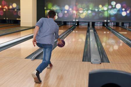 ボウリングのボールを投げるの最中に男 写真素材