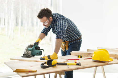 Carpenter cutting plank by circular saw  photo