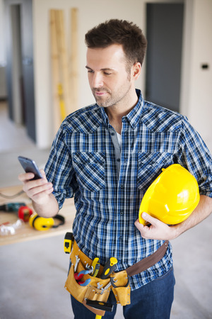 building worker: Construction worker using mobile phone during the working