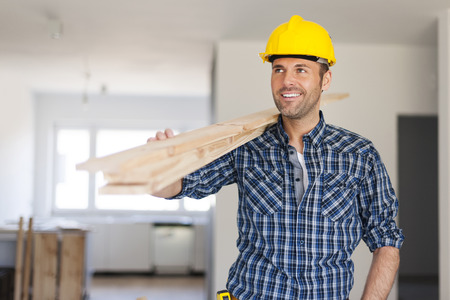 carying: Handsome man carrying wood planks  Stock Photo