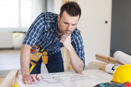 building blueprint: Building contractor bending over home plans
