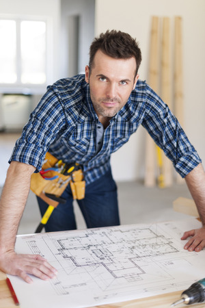 Portrait of handsome construction worker with home plans  photo