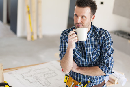 building contractor: Candid construction worker relaxing with cup of coffee Stock Photo