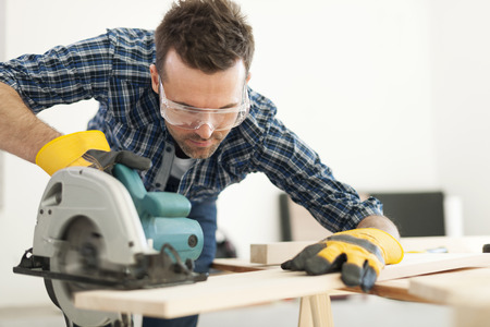 Hard working carpenter cutting wooden plank   Stock Photo