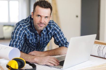 laptop stand: Portrait of construction worker at work  Stock Photo
