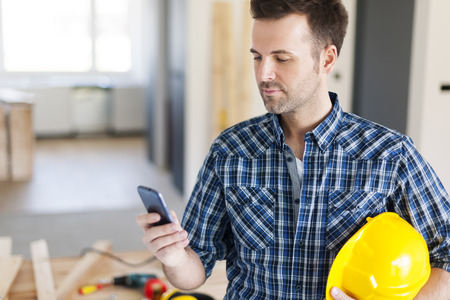 residential construction: Construction worker with contemporary mobile phone