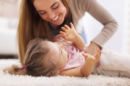 lying down on floor: Loving mother playing with little girl on carpet