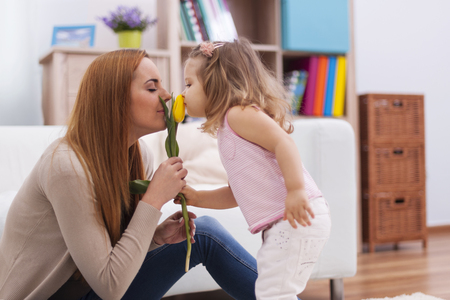 Cute little girl with her mother smelling fresh tulip photo
