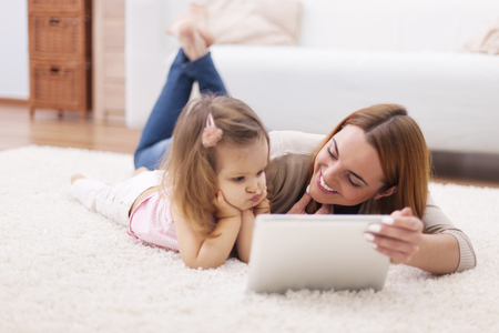 cute little girls: Focus little girl with mom using digital tablet at home