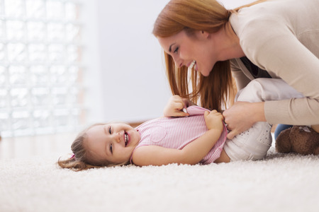 tickling: Loving mother tickling her little girl on carpet at home