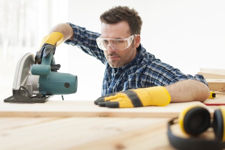 Focus carpenter cutting wooden plank photo