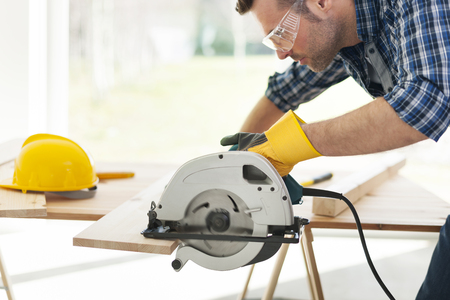 manual worker: Male carpenter sawing wooden boards
