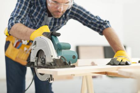 trabajando en casa: Carpintero que trabaja con la sierra circular