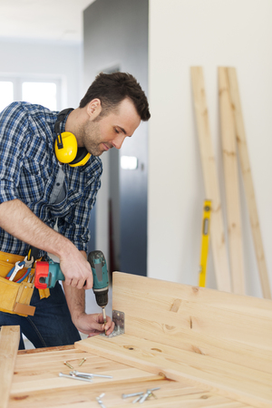 bending over: Carpenter creating new furniture   Stock Photo