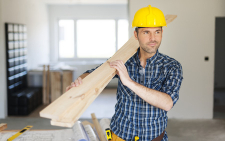 carying: Manley construction worker holding wood planks