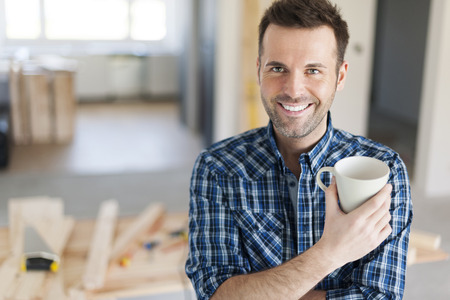 building contractor: Portrait of man drinking coffee on construction side