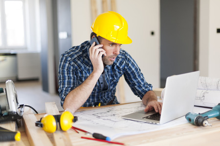 outils construction: L'homme parle au t�l�phone mobile et utilisant un ordinateur portable sur le c�t� de la construction