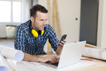 building contractor: Contemporary construction worker with electronic equipment
