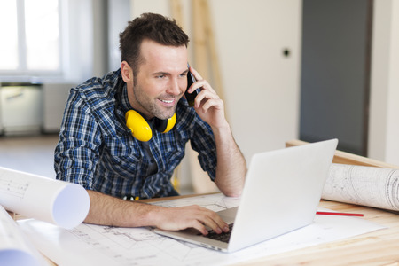 contractor: Smiling construction worker talking on mobile phone Stock Photo