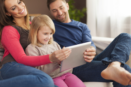 Smiling family using digital tablet at home   photo