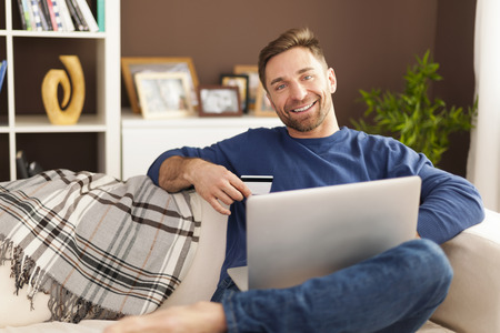 man holding card: Smiling man with laptop and credit card on sofa