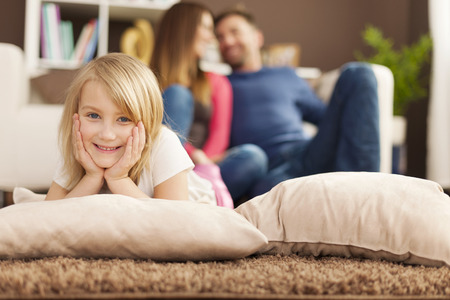 Portrait of smiling girl relaxing on carpet in living room  photo