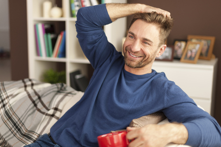 Handsome man relaxing with cup of coffee at home  photo